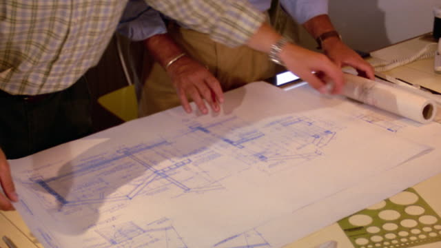 high angle ms tilt up middle aged man + younger man talking + examining blueprints on drafting table - 製図板点の映像素材/bロール