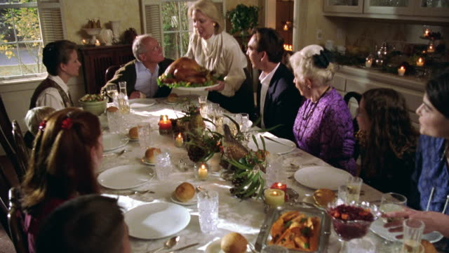 high angle tilt up multi-generational family sitting down to thanksgiving dinner with woman bringing in turkey - thanksgiving stock videos & royalty-free footage