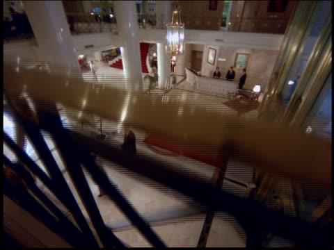 high angle tilt up of businessmen walking across floor of hotel lobby / Argentina