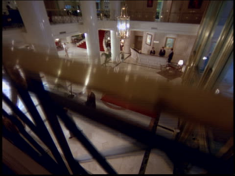 vidéos et rushes de high angle tilt up of businessmen walking across floor of hotel lobby / argentina - palace