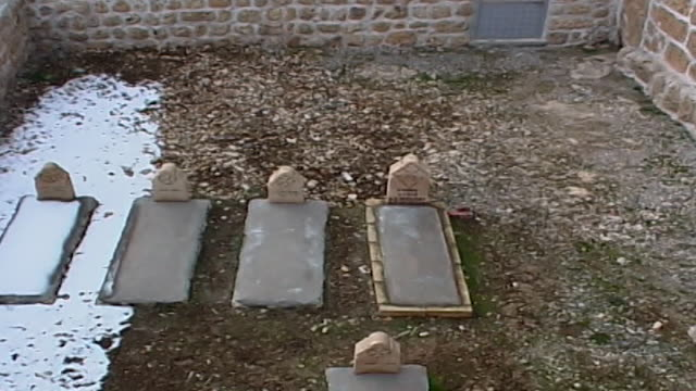 high angle tilt up of village syriac cemetery at the village of kfarbe known in turkish as gungoren. - cemetery stock videos & royalty-free footage