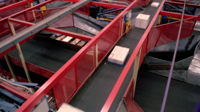 high angle tilt up pan time lapse packages being sorted on conveyor belts with workers in warehouse / memphis, tennessee - 1984 stock videos & royalty-free footage