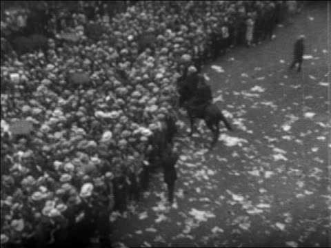 high angle tilt up police + huge crowd in rain on nyc street at rudolph valentino's funeral / newsreel - 1926年点の映像素材/bロール