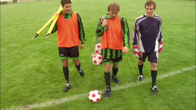 high angle tilt up soccer players walking on field carrying equipment and kicking ball - soccer glove stock videos and b-roll footage