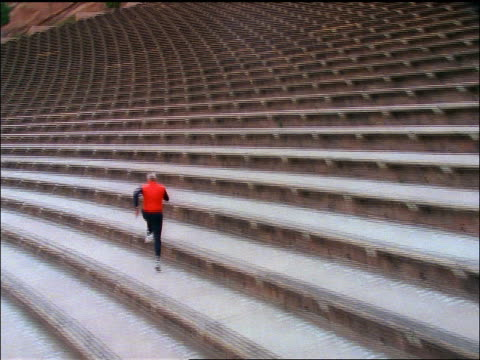 high angle tilt up zoom in man in red vest running along stadium steps away from camera / Red Rocks Amphitheater