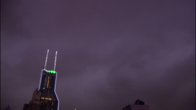 high angle tilt,down , storm clouds loom over a city illuminated by neon signs. / china - städtischer platz stock-videos und b-roll-filmmaterial