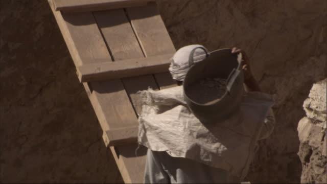high angle, tilt-up - construction workers carry buckets across a makeshift plank bridge / egypt - archäologie stock-videos und b-roll-filmmaterial