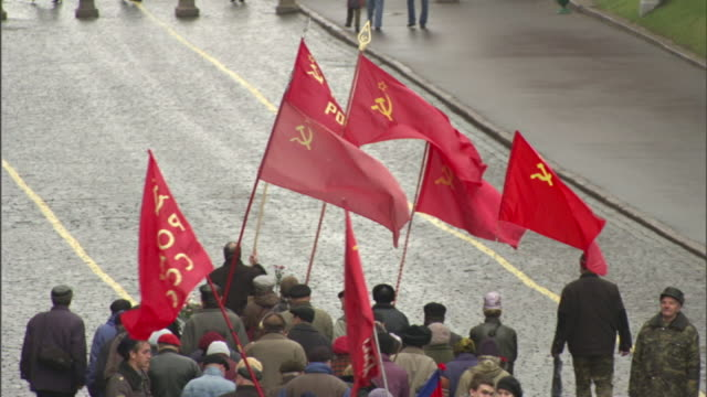 high angle tilt-up zoom-out - people march with flags in moscow's red square. / moscow, russian federation - russian culture stock videos & royalty-free footage