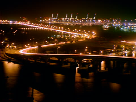 stockvideo's en b-roll-footage met high angle time lapse boats + traffic on mcarthur causeway at night / miami - macarthur causeway bridge