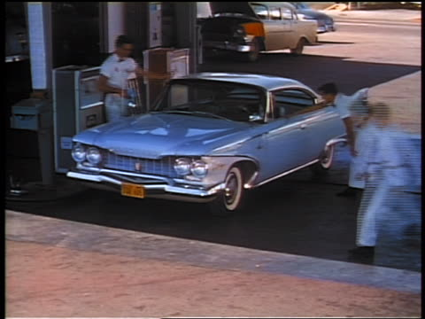 1959 high angle time lapse car pulls into service station + attendants fill gas, put air in tires, clean windshield - gas station attendant stock videos and b-roll footage