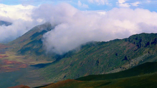 high angle time lapse clouds over mountaintops toward valley / hawaii - 1985 stock videos & royalty-free footage
