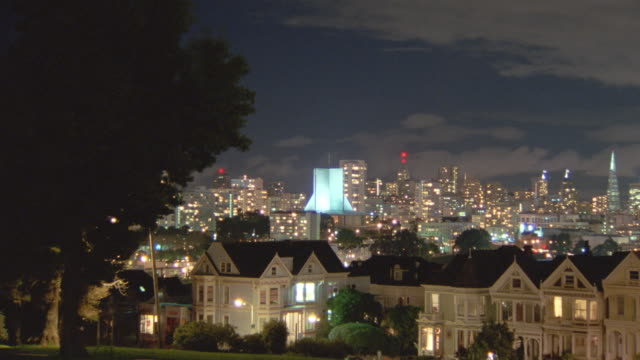 high angle PAN time lapse clouds over row of Victorian houses at night on Steiner St. / San Francisco skyline in background