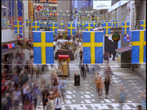 high angle time lapse people walking by shops in plaza near sergels torg / swedish flags hanging / stockholm - stockholm stock videos & royalty-free footage