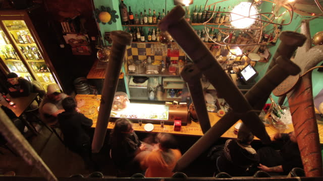 high angle time lapse shot of people in a bar in barcelona. - bartresen stock-videos und b-roll-filmmaterial