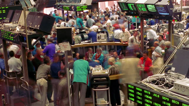 High angle time lapse traders on busy floor of commodities exchange (New York Board of Trade) / New York City