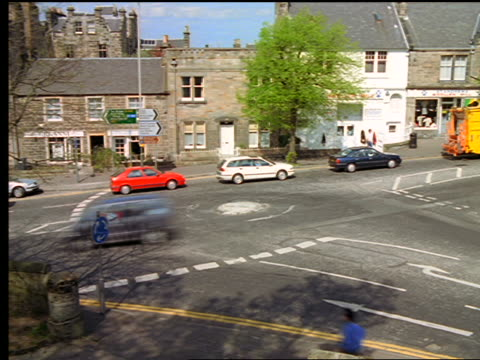 high angle time lapse traffic driving around traffic circle / st. andrews, scotland - st. andrews scotland stock videos & royalty-free footage