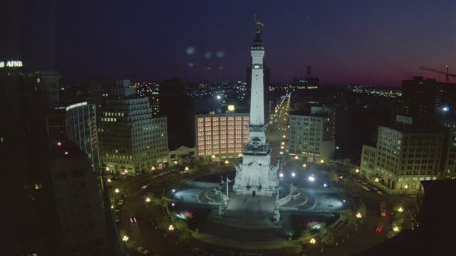 High angle time lapse traffic driving on circle around Soldiers and Sailors Monument dusk to night / Indianapolis