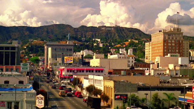High angle time lapse traffic on city street with buildings and clouds rolling over Hollywood Hills in background / Los Angeles