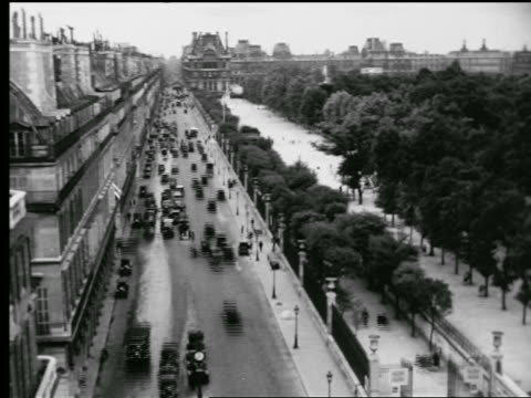 B/W 1927 high angle time lapse traffic on Rue Rivoli + people on sidewalk next to park / Louvre in background / Paris
