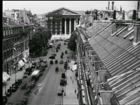 B/W 1927 high angle time lapse traffic on Rue Royale / La Madeleine (half-covered in scaffolding) in background / France