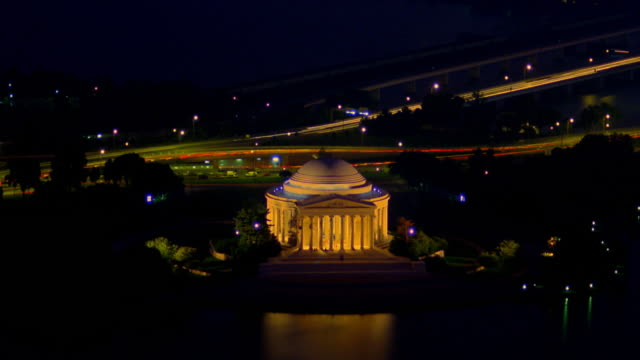 High angle time lapse traffic on streets by Jefferson Memorial at night / boats on Potomac River / Washington D.C.