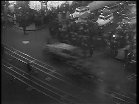 B/W 1933 high angle time lapse traffic + pedestrians crossing street in Times Square at night / NYC