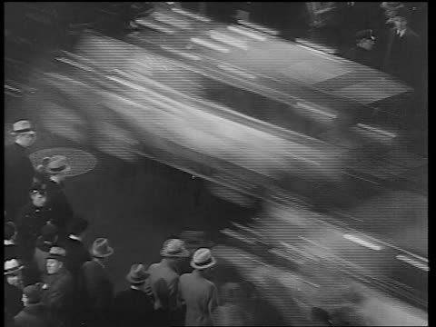 B/W 1933 high angle time lapse traffic + pedestrians crossing Times Square street at night / NYC