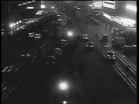 B/W 1933 high angle time lapse traffic + pedestrians in Times Square at night / NYC