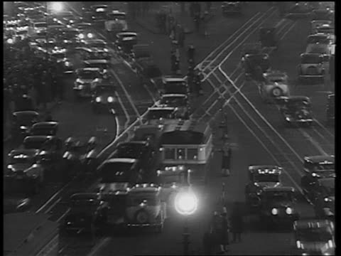 B/W 1933 high angle time lapse trolleys in traffic + pedestrians in Times Square at night / NYC