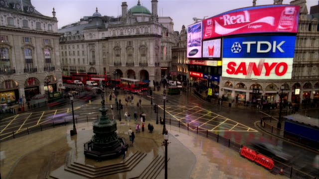 high angle time lapse wide shot traffic moving around eros statue in piccadilly circus as dusk turns to night/ london - nachtleben stock-videos und b-roll-filmmaterial