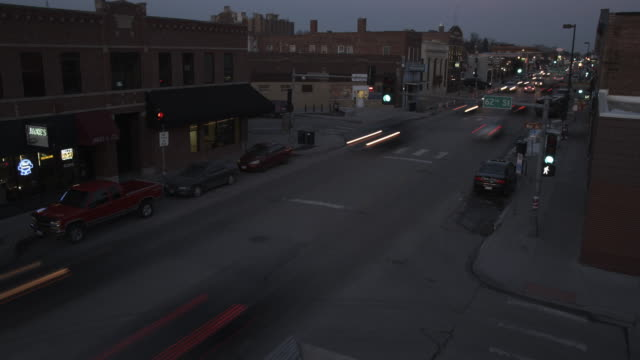 high angle timelapse of a busy small town street as the sun sets. - omaha stock videos & royalty-free footage