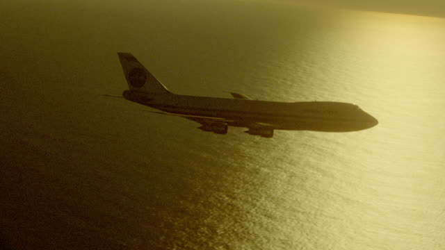 aerial backlit high angle tracking shot 747 jet flying over water with sun reflecting on water at sunset - air to air shot stock videos and b-roll footage
