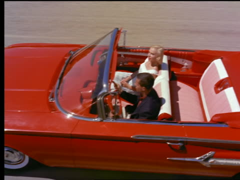 1959 high angle tracking shot couple driving in red chevrolet impala convertible - cabrio stock-videos und b-roll-filmmaterial