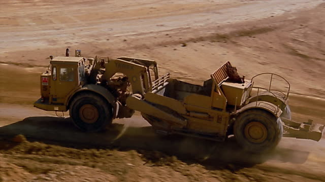 high angle tracking shot earth graders driving over quarry field - mining stock videos & royalty-free footage