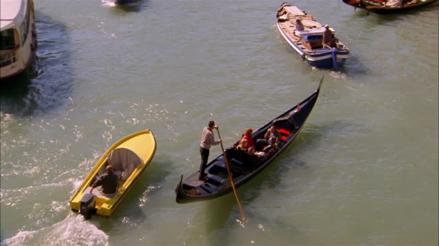 High angle tracking shot gondolier steering gondola w/motorboats passing in canal / Venice, Italy