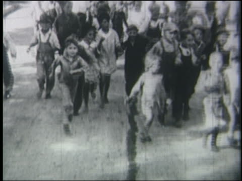 b/w 1928 high angle tracking shot large crowd of children running toward camera - 1928 stock videos & royalty-free footage