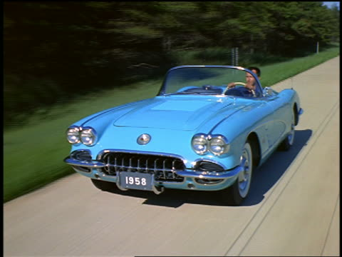 1957 high angle tracking shot man in baby blue 1957 Corvette convertible driving on road