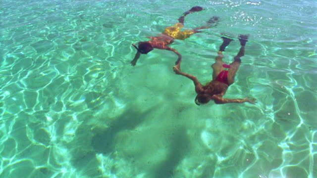 high angle tracking shot man + woman snorkeling + holding hands in clear water / Fiji