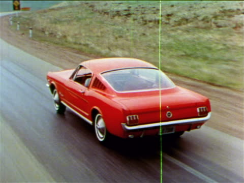 1965 high angle tracking shot red ford mustang driving on country road / industrial - ford mustang stock videos and b-roll footage