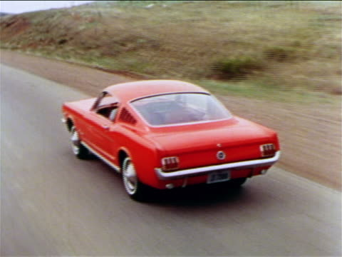 1965 high angle tracking shot red Ford Mustang driving on country road / industrial