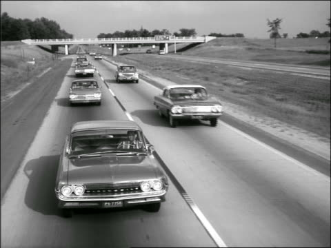 b/w 1961 high angle tracking shot traffic on highway - highway stock videos & royalty-free footage