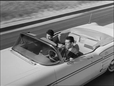 vídeos de stock e filmes b-roll de b/w 1958 high angle tracking shot zoom out couple driving chevrolet impala convertible on rural highway - general motors