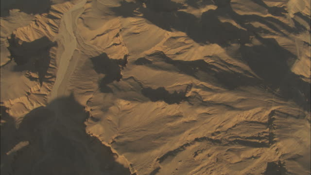 High Angle, tracking-left - Dry riverbeds wind through desert mountains / Egypt