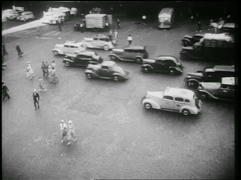 vídeos de stock, filmes e b-roll de b/w 1939 high angle traffic + pedestrians on cobblestone city street / nyc / documentary - high street
