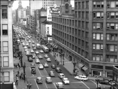 vídeos de stock, filmes e b-roll de b/w 1957 high angle traffic + pedestrians on market street / philadelphia - 1950