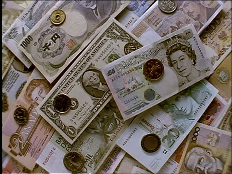 high angle turning close up of international money (bills + coins) - 国際金融点の映像素材/bロール