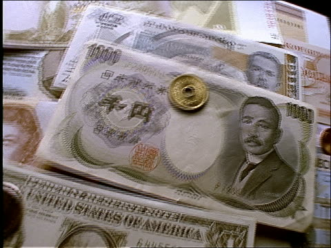 high angle turning close up of international money (bills + coins)