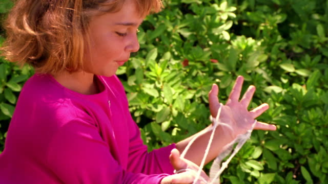 """canted high angle ms two girls playing """"cat's cradle"""" with string outdoors - hair band stock videos and b-roll footage"""