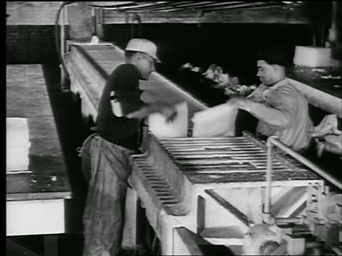 b/w 1929 high angle two men taking sheets of wax from racks in factory / newsreel - 1929 stock videos & royalty-free footage