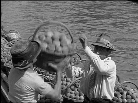 b/w 1930 high angle pan two men unloading baskets of fruit from boat / one man puts basket on head / venice - italian culture stock videos & royalty-free footage